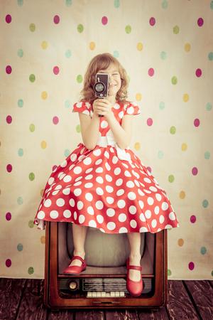retro cinema: Child playing at home. Kid holding retro camera. Cinema concept