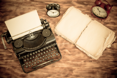ancient telephone: Retro typewriter with paper blank on wood background. Top view