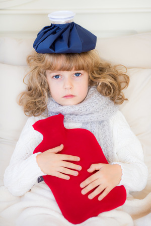 hot water bottle: Sick child with fever and hot water bottle at home Stock Photo