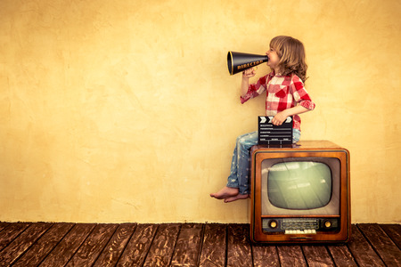 camera: Kid shouting through vintage megaphone. Communication concept. Retro TV