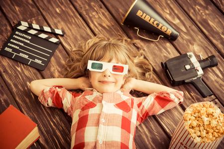 palomitas: Niño que juega en casa. Kid con objetos de cine de época. Concepto de entretenimiento. Vista superior