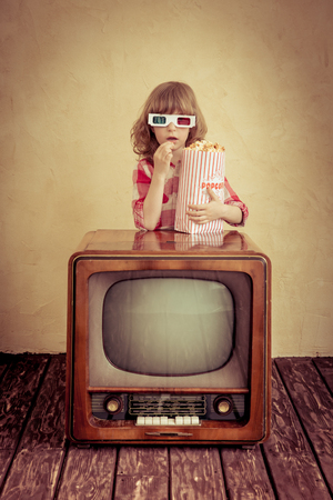 surprised kid: Child playing at home. Surprised kid eating popcorn on retro TV. Cinema concept