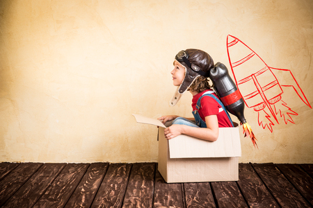 Kid with jet pack. Child playing at home. Success, leader and winner concept Archivio Fotografico