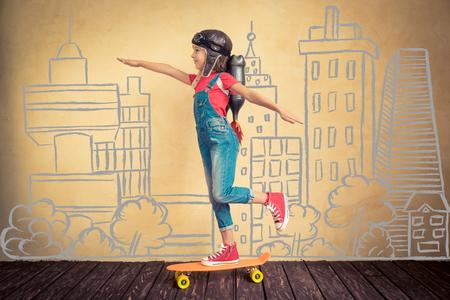 スケート ボードに乗ってジェット パックとの子供します。子は、自宅で再生します。成功、リーダーおよび勝者の概念