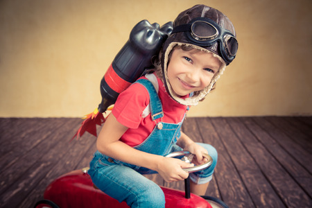 packs: Kid with jet pack driving retro toy car. Child playing at home. Success, leader and winner concept