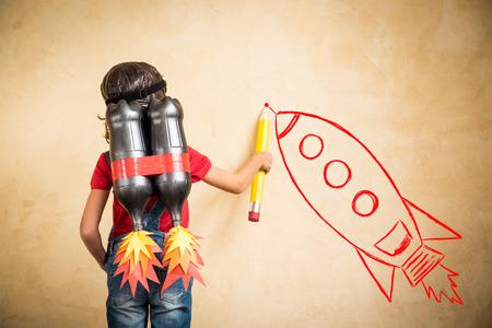 Kind mit Jet-Pack zeichnen Skizze an der Wand. Kind beim Spielen zu Hause. Erfolg, Marktführer und Gewinner-Konzept