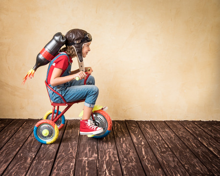 lideres: Cabrito con la moto jet pack equitación. Niño que juega en casa. Éxito, líder y ganador concepto Foto de archivo
