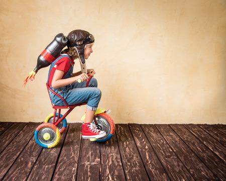Kid com andar de bicicleta bloco do jato. Criança que joga em casa. Sucesso, líder e conceito do vencedor