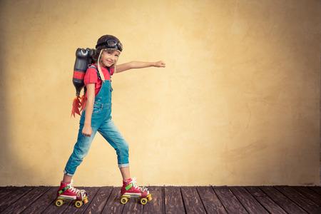 Kid s jet pack jízdě na kolečkových bruslích. Dítě hraje doma. Úspěch, vůdce a vítěz koncepce Reklamní fotografie
