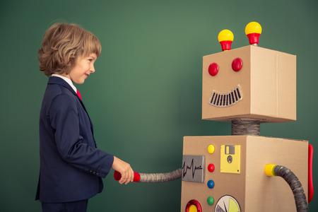 Kind mit Spielzeugroboter in der Schule. Erfolg und Innovation Technologie-Konzept