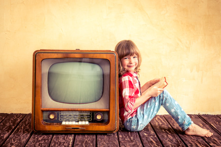 아이는 집에서 놀고. 복고풍 TV 근처 책을 읽고 아이. 시네마 개념