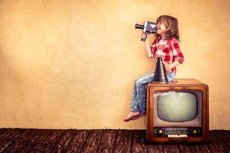 television antigua: Niño que juega en casa. Cabrito que hace una película con la cámara retra. Concepto Cine Foto de archivo