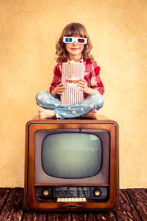 retro tv: Child playing at home. Kid sitting on retro TV and eating popcorn. Cinema concept