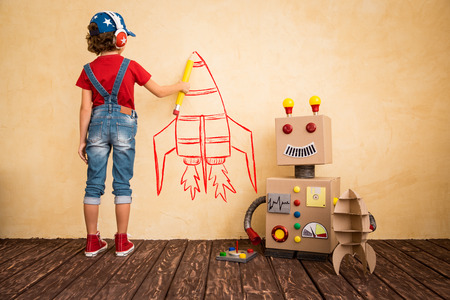 pilot light: Happy child playing with toy robot at home. Innovation technology and success concept Stock Photo