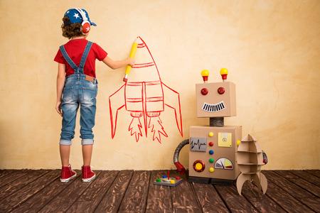 COHETES: Niño feliz que juega con el robot de juguete en casa. La innovación tecnológica y el concepto de éxito
