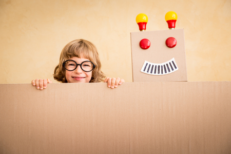 niños con pancarta: Chico friki divertido con el robot de juguete. La innovación tecnológica y el concepto de éxito. En blanco, con copia espacio para el texto Foto de archivo
