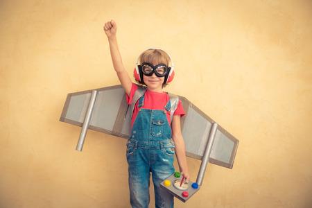 Glückliches Kind spielt mit Spielzeug-Jetpack zu Hause. Erfolg und Marktführer Konzept Lizenzfreie Bilder
