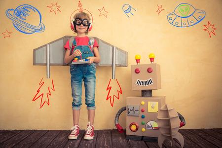 Gelukkig kind spelen met speelgoed robot thuis. Innovatie technologie en succes concept Stockfoto