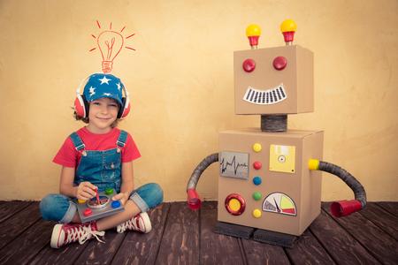 niño modelo: Cabrito feliz que juega con el robot de juguete en casa. Retro tonificado