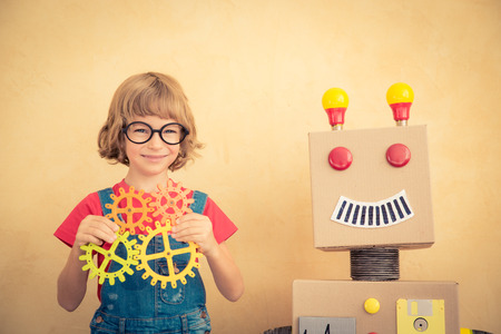 robot girl: Funny nerd child with toy robot. Innovation technology and success concept Stock Photo