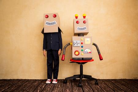 Porträt der jungen Geschäftsmann mit Spielzeugroboter in moderne Loft-Büro. Erfolg, Kreativität und Innovation-Technologie-Konzept. Kopieren Sie Platz für Ihren Text