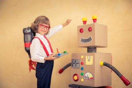 robot: Portrait of young businessman with toy robot in modern loft office. Success, creative and innovation technology concept. Copy space for your text