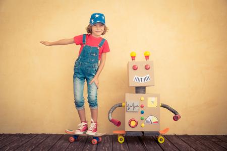 niño modelo: Niño feliz que juega con el robot de juguete en casa. Retro tonificado Foto de archivo