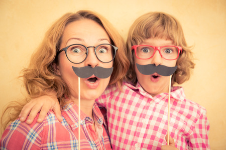 nerd glasses: Mother and child with fake mustache. Happy family playing in home Stock Photo