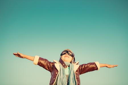 piloto: Kid piloto contra el fondo del cielo de otoño. Niño feliz jugando al aire libre. Retro tonificado