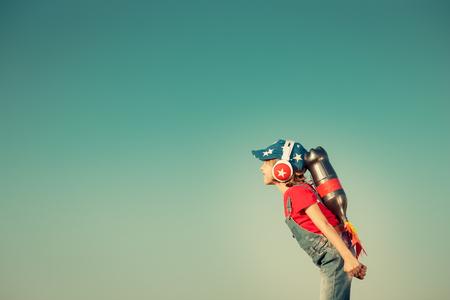 Cabrito con el jet pack contra fondo del cielo de otoño. Niño que juega al aire libre. Éxito, líder y ganador concepto. Retro tonificado