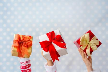 tomados de la mano: Feliz Navidad. Manos de los ni�os que sostienen los rect�ngulos de regalo de Navidad contra azul polka dot fondo. Vacaciones de invierno concepto Foto de archivo