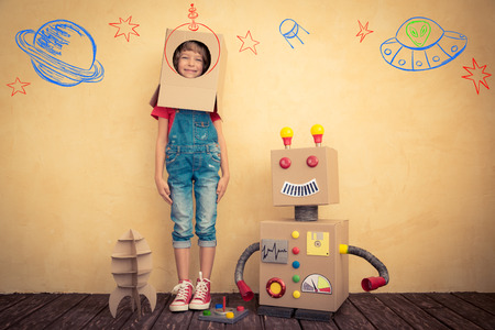 innovación: Cabrito feliz que juega con el robot de juguete en casa. La innovación tecnológica y el concepto de éxito