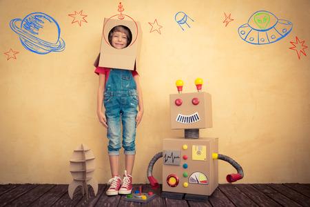 Erfolg: Glückliches Kind, das mit Spielzeugroboter zu Hause. Innovation Technologie und Erfolgskonzept