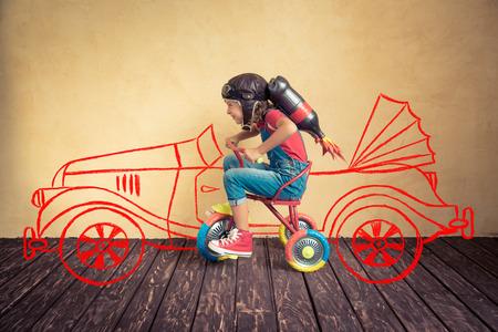 imaginacion: Cabrito con la moto jet pack equitación. Niño que juega en casa. Éxito, líder y ganador concepto Foto de archivo