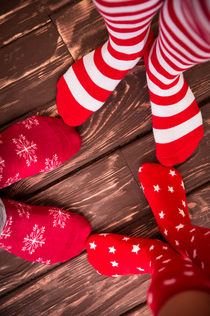 socks child: Feet wearing Christmas socks on wood floor. Happy family at home. Xmas holidays concept