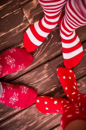 calcetines: Pies llevaba calcetines de Navidad en el piso de madera. Familia feliz en el hogar. Navidad concepto de vacaciones
