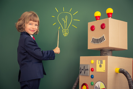 Kid with toy robot in school. Success and innovation technology concept
