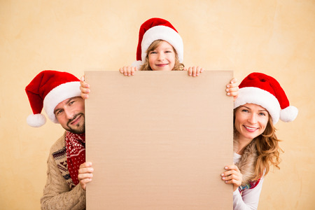 home decorations: Happy family holding Christmas poster blank. Xmas holiday concept