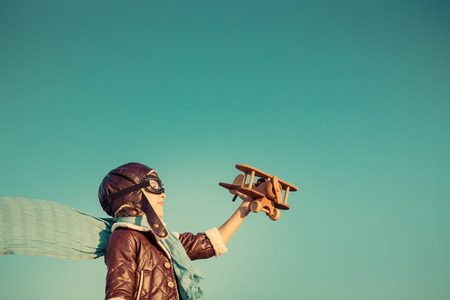 piloto: Piloto Kid con avión de juguete de madera contra el fondo del cielo de otoño. Niño feliz jugando al aire libre. Retro tonificado