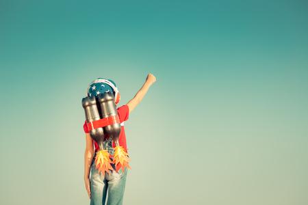 bambini: Bambino con jet pack contro il cielo di sfondo autunnale. Bambino che gioca all'aperto. Successo, leader e vincitore concetto. Retro tonica Archivio Fotografico