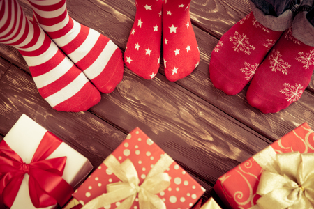 holidays: Feet of family on wood floor. Christmas holidays concept