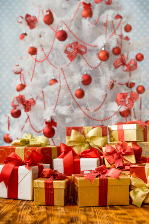 cajas navideñas: Christmas gift boxes against tree with decorations. Xmas holiday concept