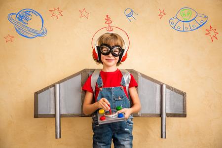 geek: Kid piloto jugando con jetpack juguete en casa. El �xito y el concepto de l�der Foto de archivo