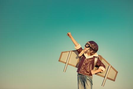 秋の空の背景に対してグッズ ジェット パックを持つ子供パイロット。野外で遊ぶ幸せな子