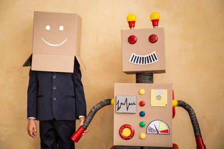 テクノロジー: モダンなロフト オフィスでおもちゃのロボットで青年実業家の肖像画。成功、創造と革新の技術コンセプト。テキストのコピー スペース