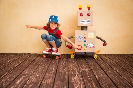 robot: Cabrito feliz que juega con el robot de juguete en casa. Retro tonificado