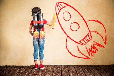 concept: Bambino con schizzo di jet pack schizzo sulla parete. Bambino che gioca a casa. Concetto di successo, leader e vincitore