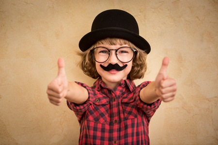 geek: Funny kid with fake mustache. Happy child playing in home Stock Photo