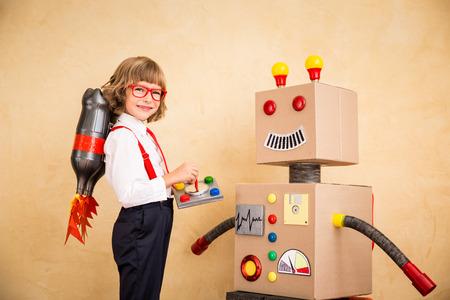 モダンなロフト オフィスでおもちゃのロボットで青年実業家の肖像画。成功、創造と革新の技術コンセプト。テキストのコピー スペース