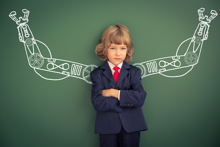 child education: Kid with drawn robot hands against blackboard. Schoolchild in class Stock Photo